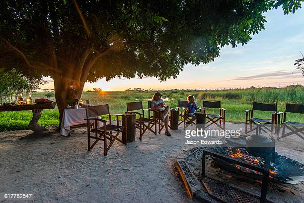 A mother and son sitting around a campfire at dawn in a luxury safari camp.