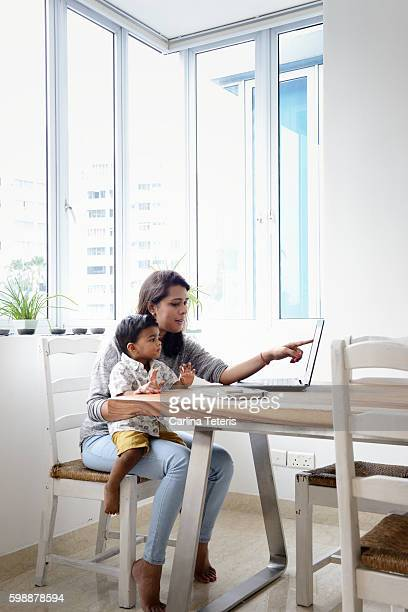 Mother and son sitting at a dining table working on a laptop