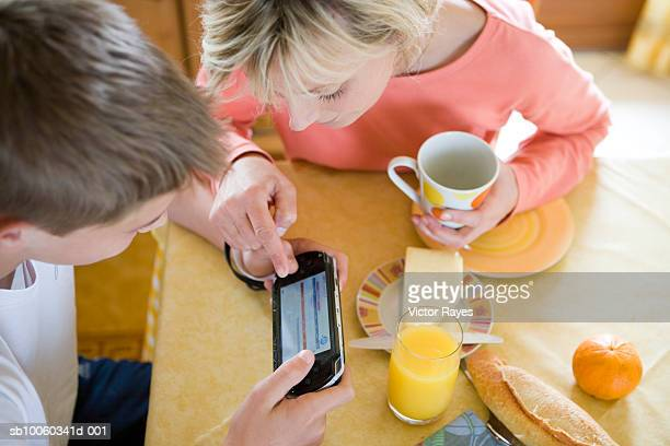Mother and son (10-11 years) sitting at kitchen table using electronic organiser, elevated view