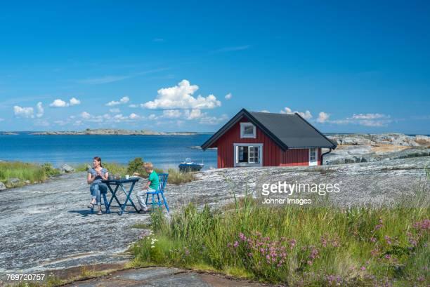 mother and son sitting at rocky coast - arquipélago - fotografias e filmes do acervo
