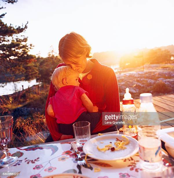 Mother and son sitting at table in backyard