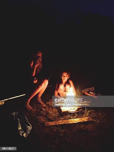 Mother And Son Sitting By Bonfire At Night