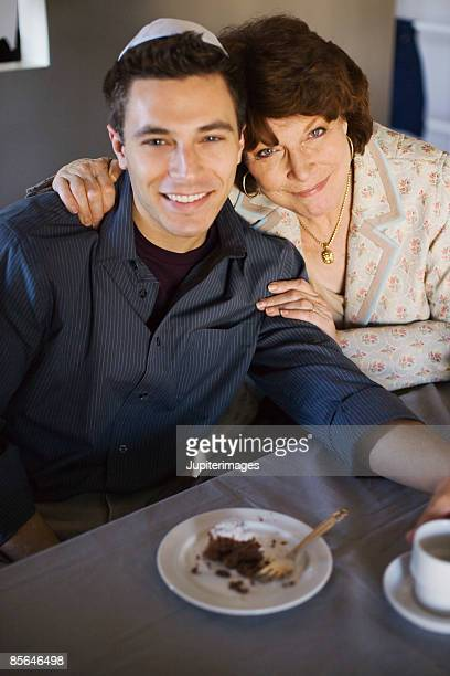 Mother and son sitting in front of slice of chocolate cake