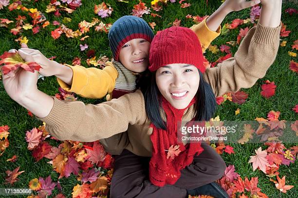 Mother and son sitting on autumn leaves