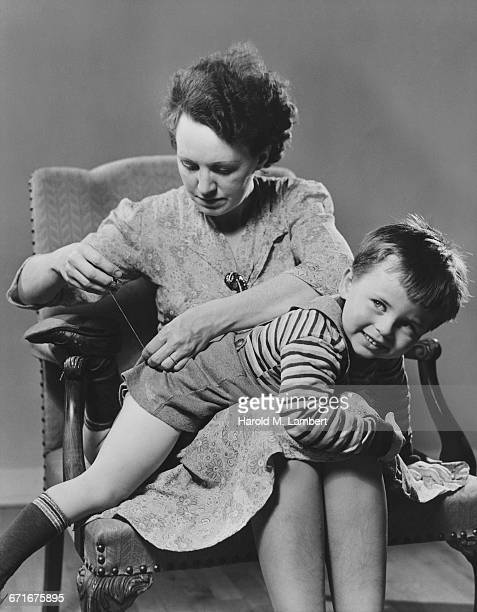 mother and son sitting on chair and stitching  - {{relatedsearchurl(carousel.phrase)}} ストックフォトと画像