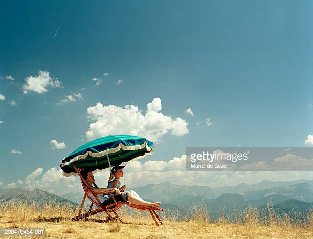 Mother and son (5-7) sitting on deckchair in mountainous landscape