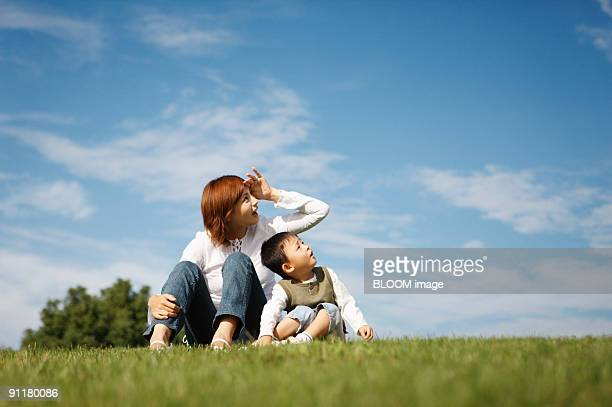 Mother and son sitting on grass, looking upward