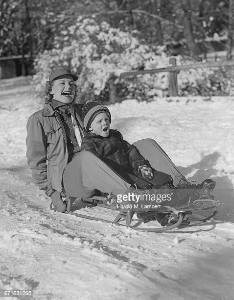 mother and son sitting on snowboard - {{relatedsearchurl(carousel.phrase)}} ストックフォトと画像