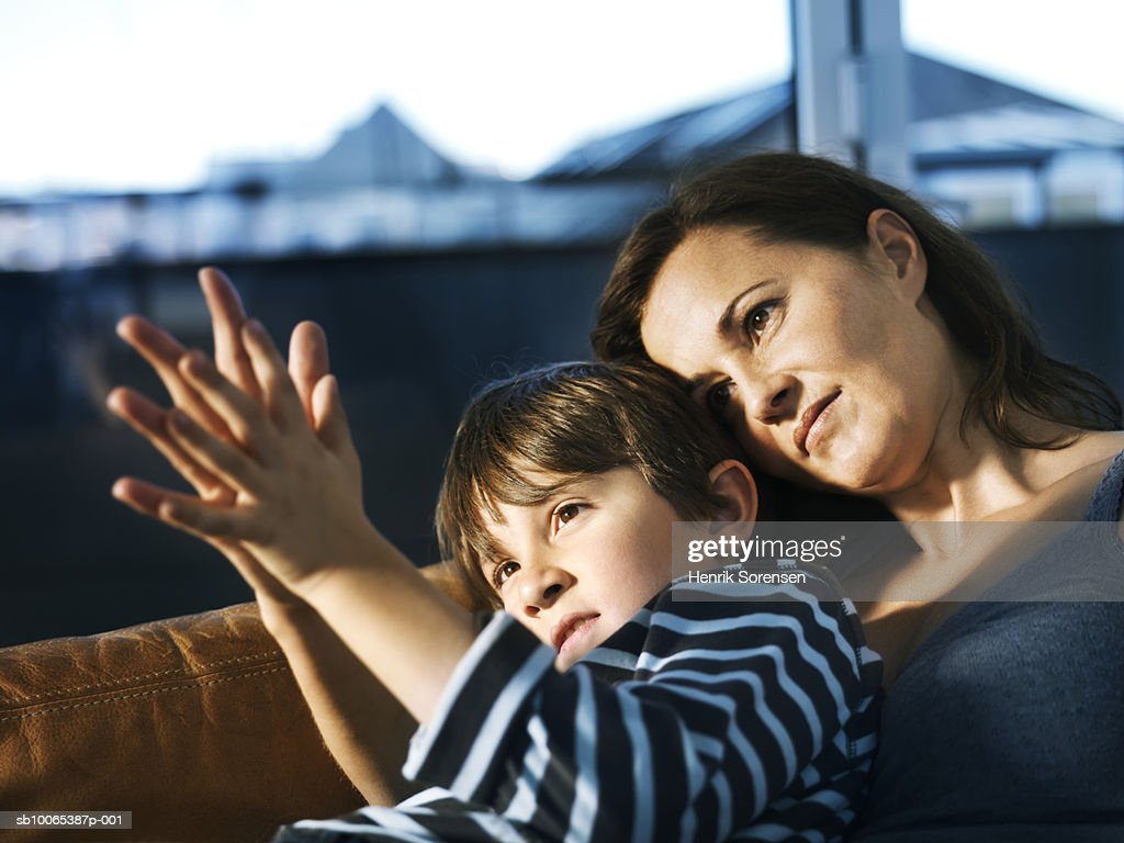 Mother and son (8-9) sitting on sofa, comparing palms : Foto stock