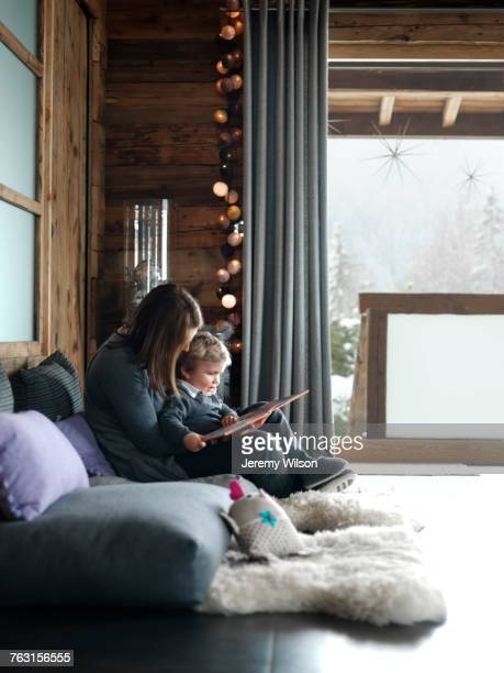 Mother and son, sitting on sofa, reading book
