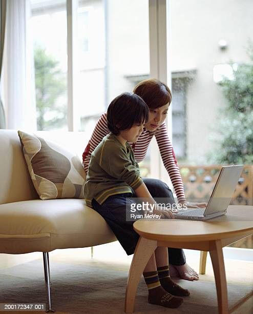 Mother and son (4-6) sitting on sofa, using laptop, side view