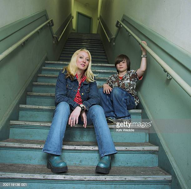 Mother and son (8-10) sitting on stairway, portrait