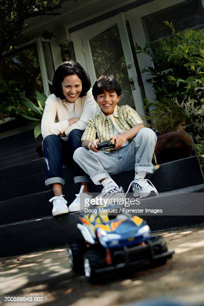 mother and son (6-7) sitting on steps, looking at toy car - remote controlled car stock pictures, royalty-free photos & images