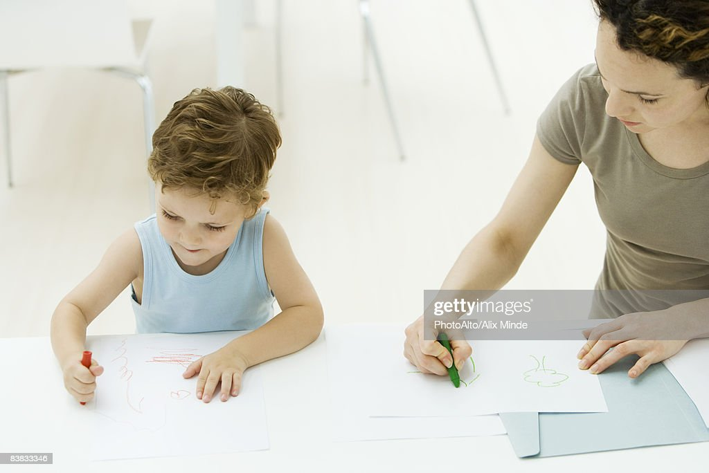 Mother And Son Sitting Side By Coloring With Crayons Stock Photo
