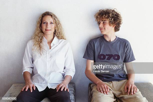Mother and son sitting side by side