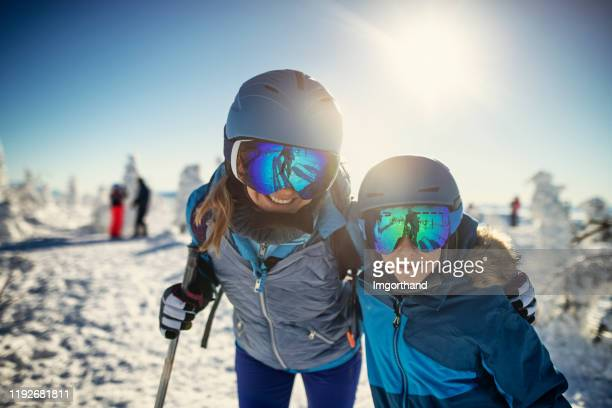mother and son skiing on beautiful sunny winter day - ski holiday stock pictures, royalty-free photos & images