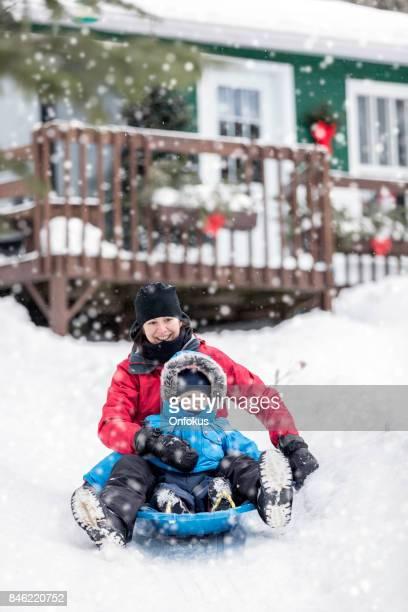 Mother and Son Sledding on Snow at Christmas