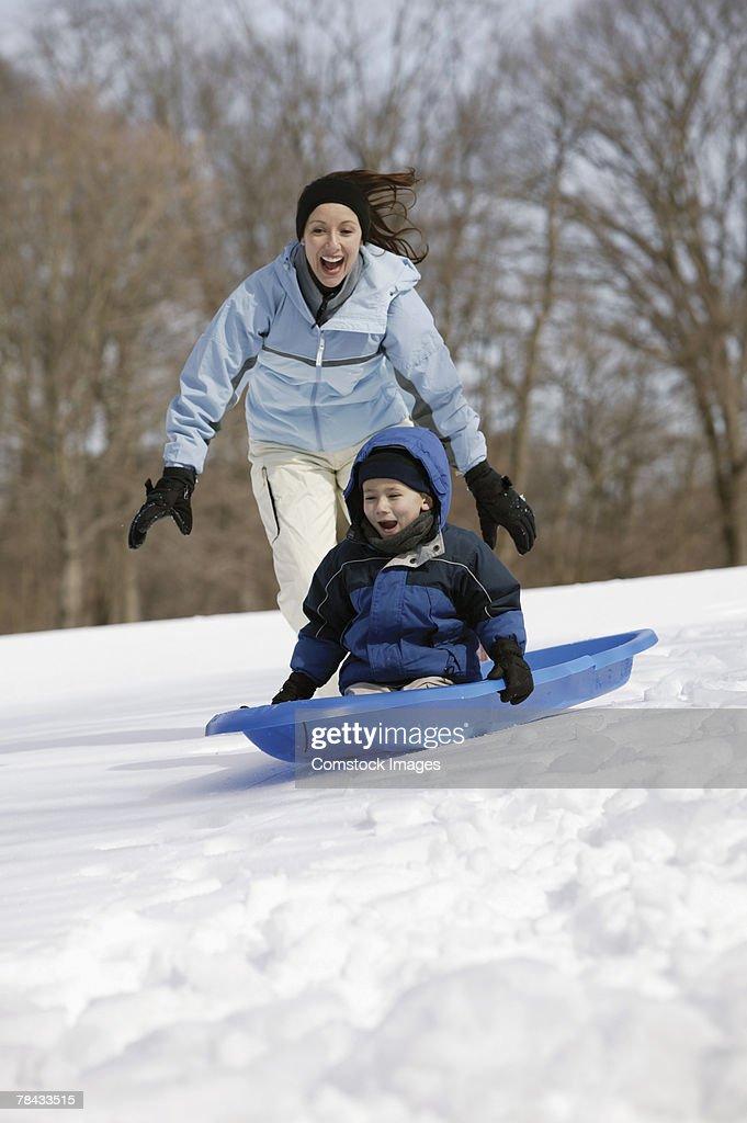 Mother and son sledding : Stockfoto