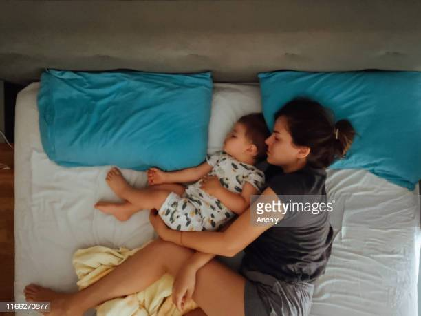 mother and son sleeping in bed - toddler stock pictures, royalty-free photos & images