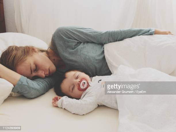 mother and son sleeping on bed at home - 2 5 mesi foto e immagini stock