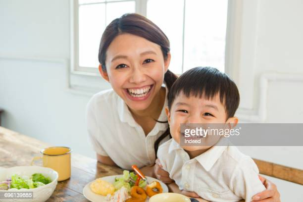 Mother and son smiling at table