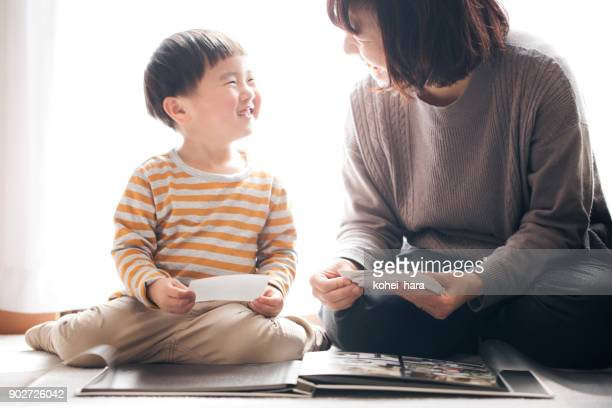 mother and son smiling together while making photo album - photo album stock photos and pictures