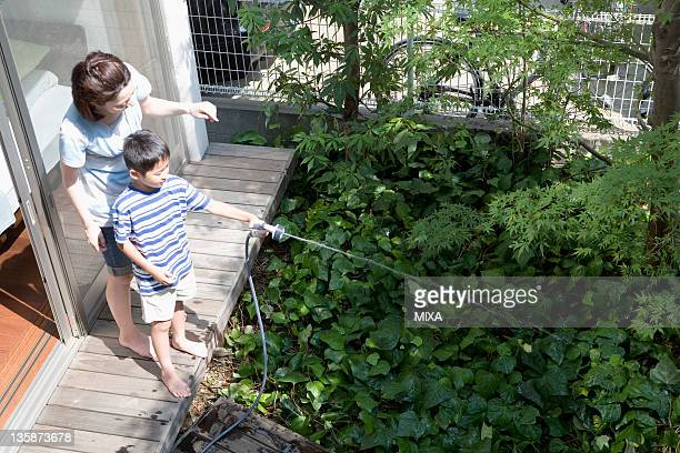 Mother and son sprinkling water