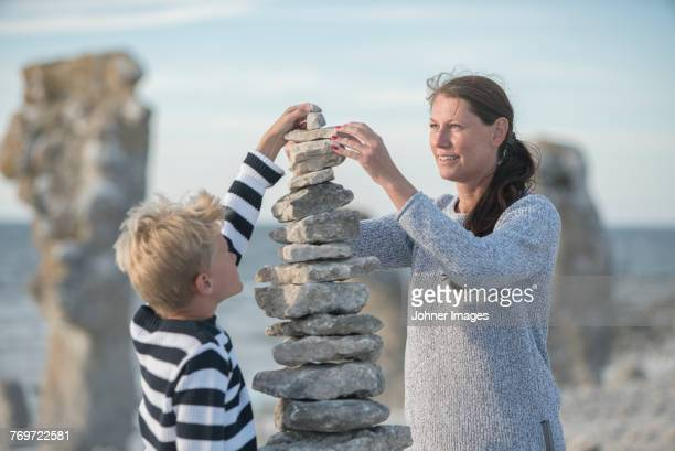 Mother and son stacking rocks