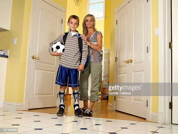 Mother and son (8-10) standing in doorway at home, portrait