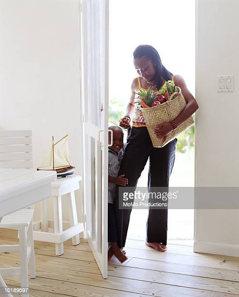 mother and son (6-8 years) standing in doorway, mother holding bag of - 25 29 years stock pictures, royalty-free photos & images
