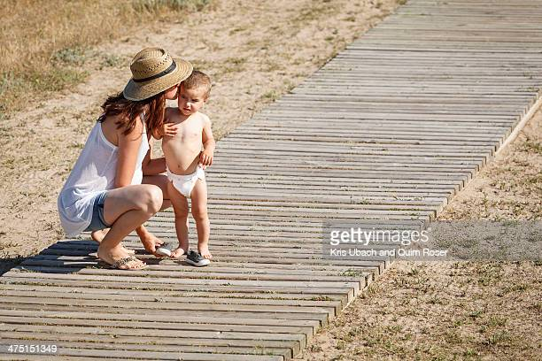 Mother and son standing on boardwalk, kissing cheek