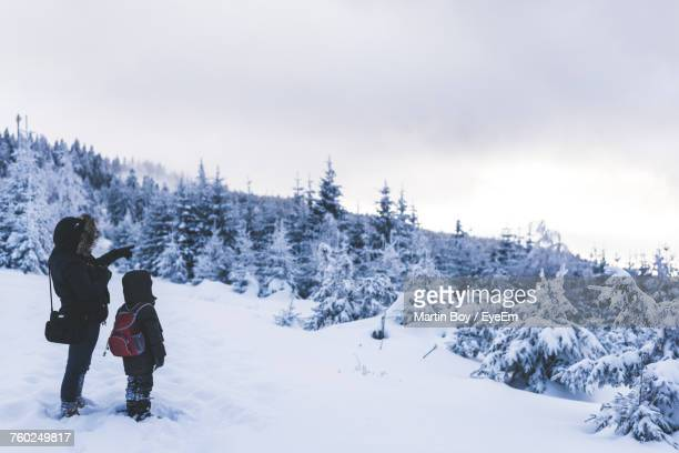 Mother And Son Standing Standing On Snowy Hill Against Sky
