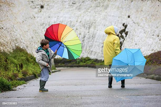 Mother and son struggling with umbrellas in wind