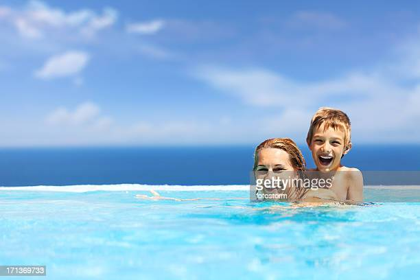Mother and son swimming in infinity pool
