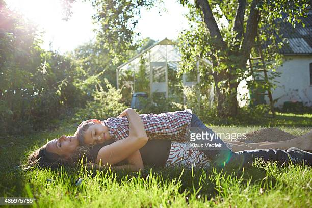 Mother and son taking a nap in their green garden