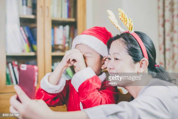 Mother and son taking self photography in Christmas celebration