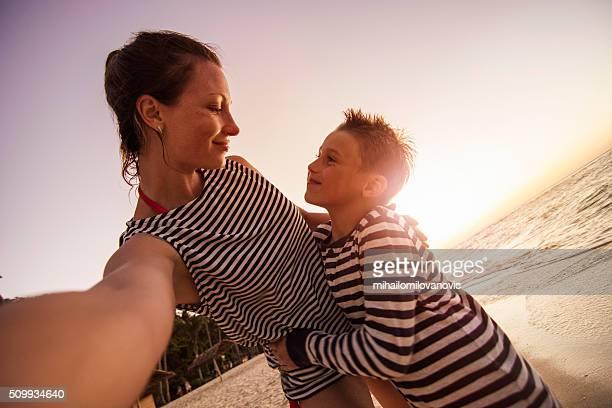 母と息子ビーチのセルフィーを取る