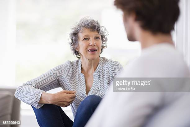 Mother and son talking in living room