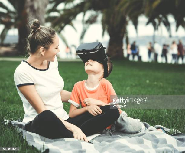 Mother and son testing Virtual Reality simulator on the street