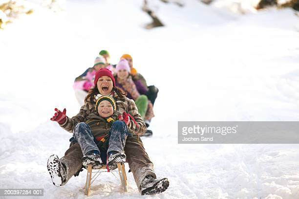 mother and son (8-10) tobogganing in snow, family in background - fun stock pictures, royalty-free photos & images