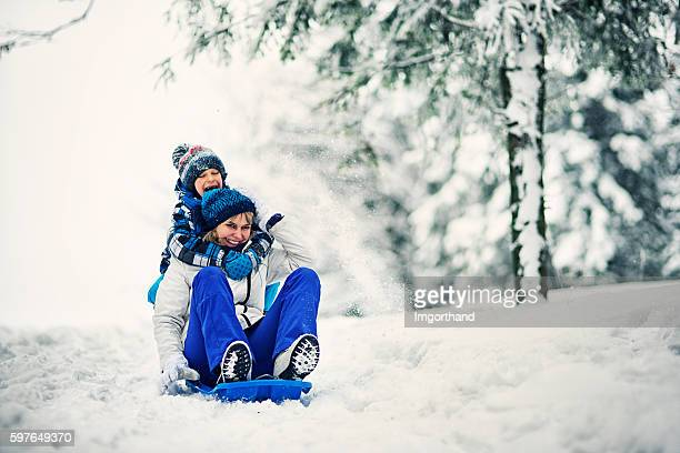 Mother and son tobogganing in winter forest