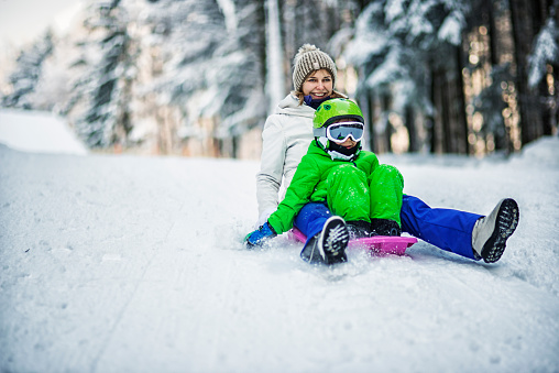 Mother and son tobogganing in winter forest 623859618