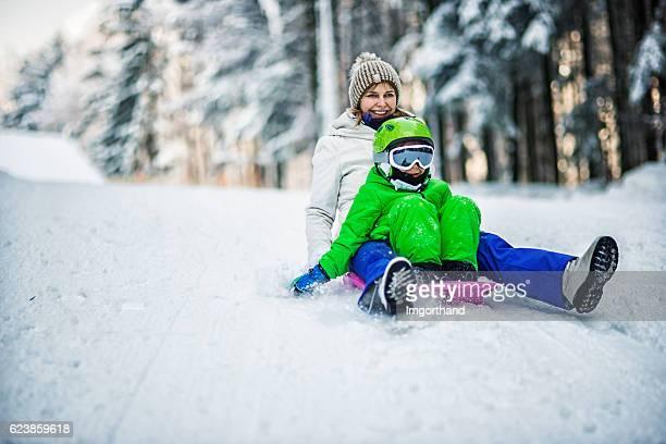 Mère et son fils de toboggan en hiver forêt
