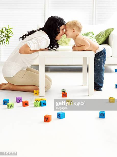 Mother and son touching foreheads in a playroom
