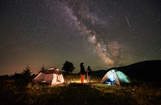 Mother and son tourists resting at camping in mountains at night sky full of stars and Milky way 948512452
