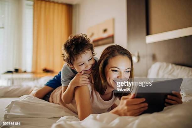 mother and son using a digital tablet - hotel stock pictures, royalty-free photos & images