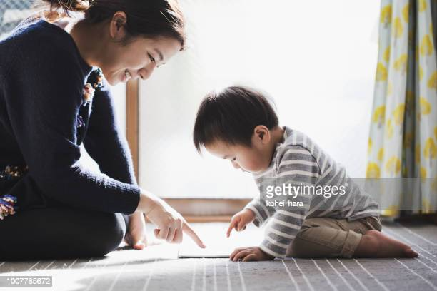 mother and son using a digital tablet together - childhood stock pictures, royalty-free photos & images
