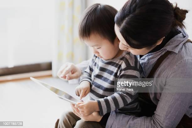 母と息子が一緒にデジタル タブレットを使用して - シングルマザー ストックフォトと画像