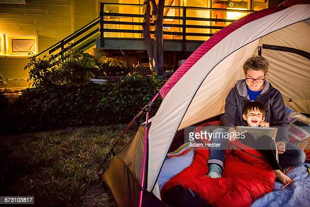 Mother and son using digital tablet in backyard tent