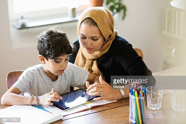 Mother and son using digital tablet while studying at home